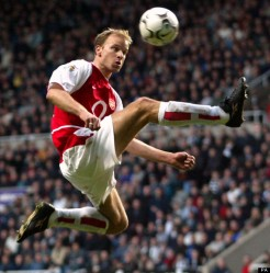 Arsenal's Dennis Bergkamp (l) jumps to control the ball as Newcastle United's Andy O'Brien (r) looks on